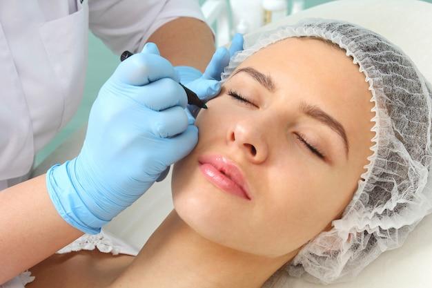 Preparazione del viso del paziente a una procedura cosmetica.