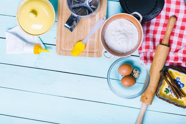 Preparazione dell'impasto. ingredienti per l'impasto - uova e farina con il mattarello. su fondo in legno.