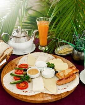 Preparazione della colazione con piatto per la colazione, succo d'arancia e teiera