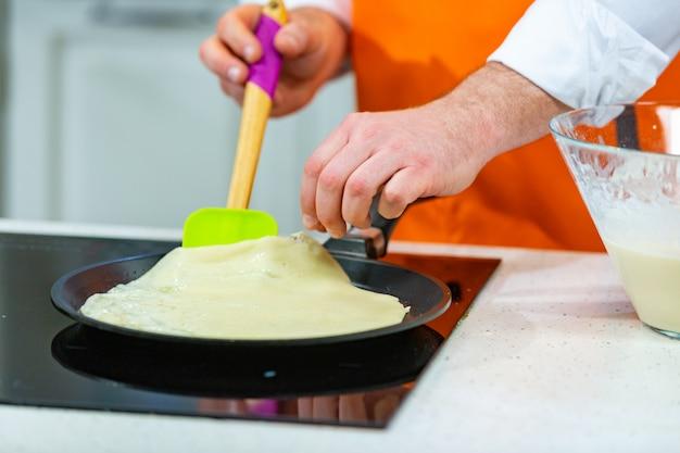 Preparazione della cucina: lo chef frigge frittelle fresche in due padelle
