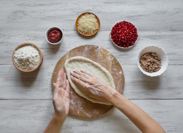 Preparazione della tradizionale pizza araba manaqish con carne e melograno.