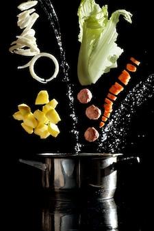 Preparazione della zuppa, verdure che volano antigravità nell'aria sopra la zuppa