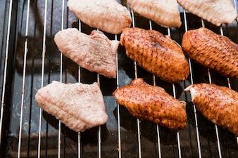 Preparazione di ali di pollo su griglia metallica