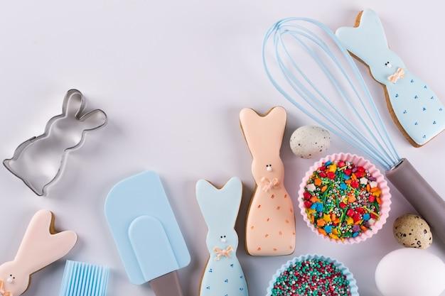Preparazione di biscotti al panpepato. biscotti pasquali a forma di coniglio divertente, strumenti necessari per fare la pasta di pan di zenzero, granelli colorati. concetto di pasqua.