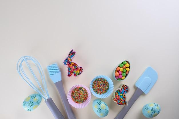 Preparazione di biscotti al panpepato. tagliabiscotti pasquali, strumenti necessari per fare la pasta di pan di zenzero, granelli colorati. concetto di pasqua.