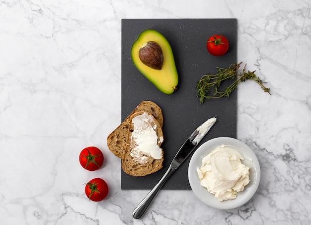 Preparazione di panini sani con crema di formaggio, avocado, pomodori e timo.