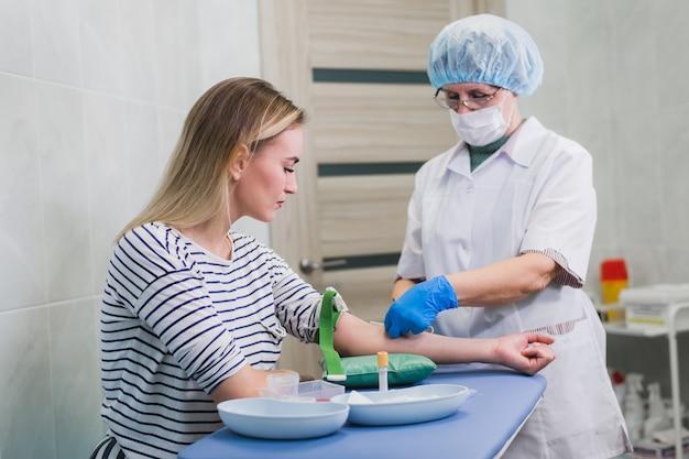 Preparazione per analisi del sangue con una donna bionda abbastanza giovane dal medico femminile in uniforme medica delle camice sul tavolo nella stanza luminosa bianca. l'infermiera perfora la vena del braccio del paziente con un tubo vuoto dell'ago.