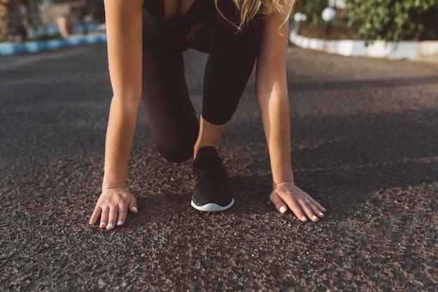 Preparazione per correre, inizio di bella donna, mani vicino ai piedi in scarpe da ginnastica per strada. motivazione, mattina di sole, stile di vita sano, ricreazione, formazione, lavoro a domicilio