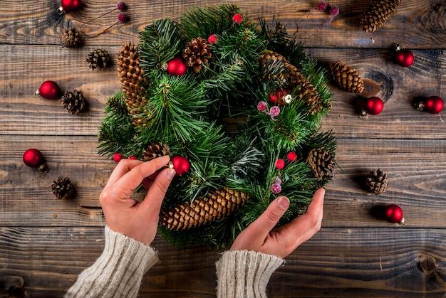Preparazione per le vacanze di natale. donna che decora la corona verde di natale con le pigne e bacche rosse di inverno e palle dell'albero di natale