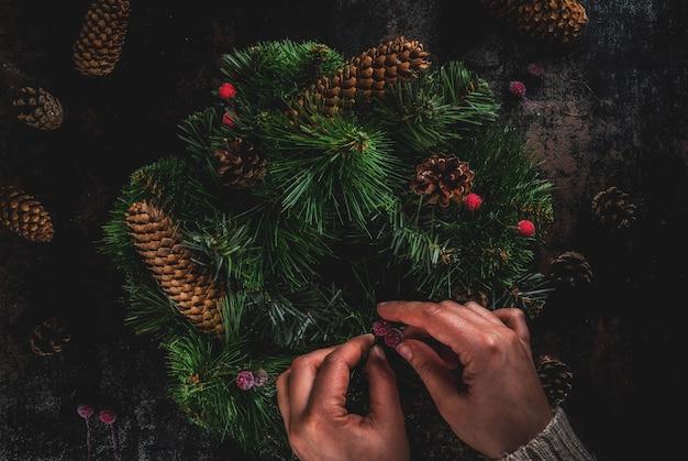 Preparazione per le vacanze di natale. donna che decora la corona verde di natale con le pigne e le bacche rosse di inverno, sul copyspace arrugginito scuro e di vista superiore, mani femminili