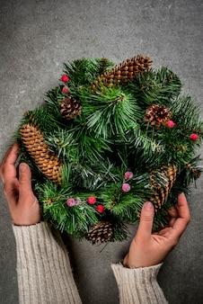 Preparazione per le vacanze di natale. donna che decora la corona verde di natale con le pigne e le bacche rosse di inverno