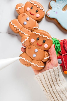 Preparazione per natale la ragazza (le mani nella foto) decora il pan di zenzero tradizionale fatto in casa fatto a mano con biscotti di glassa di zucchero multicolore tavolo in marmo bianco