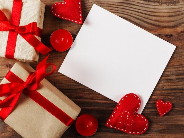 Preparazione per san valentino. cuori rossi e regali artigianali su legno. copia spazio