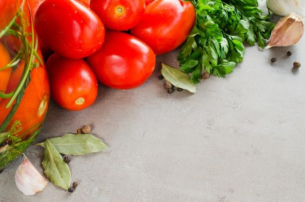 Preparazione pomodori marinati conservazione con erbe, aglio, sale e spezie.