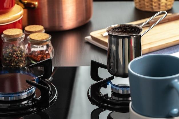 Prepari il caffè in un turco d'acciaio su una fine della stufa di gas su