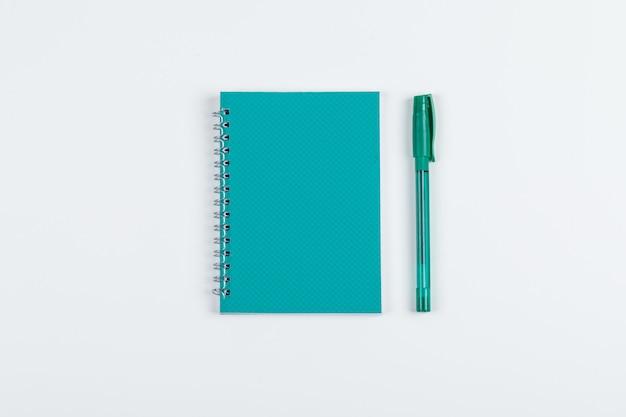Presa delle note e concetto del taccuino con la penna sulla disposizione piana del fondo bianco. immagine orizzontale