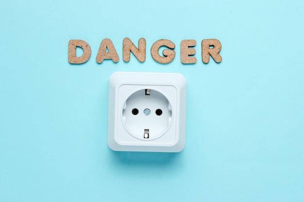 Presa di corrente con la parola pericolo sulla superficie blu.