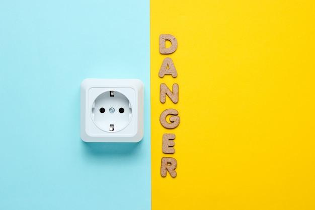 Presa di corrente con la parola pericolo sulla superficie gialla blu.
