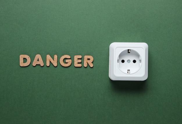 Presa di corrente con la parola pericolo sulla superficie verde.