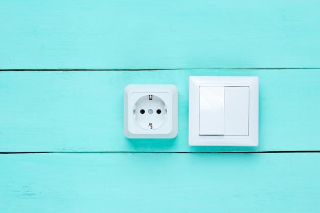 Presa di corrente e interruttore sulla parete di legno blu,