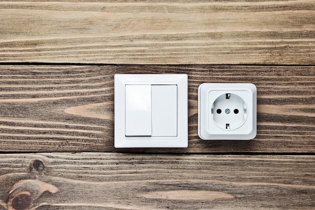 Presa di corrente e interruttore sulla parete di legno,