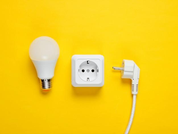 Presa di corrente in plastica bianca, spina di alimentazione, lampadina a led. vista dall'alto