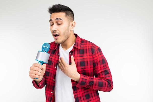 Presentatore maschio con un microfono in mano ha mal di gola su uno sfondo bianco studio isolato