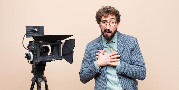 Presentatore televisivo che sembra triste, ferito e affranto, tenendo entrambe le mani vicine al cuore, piangendo e sentendosi depresso