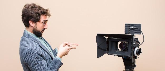 Presentatore televisivo in piedi e indicando un oggetto sullo spazio della copia, vista posteriore