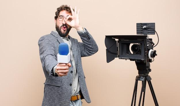 Presentatore televisivo sorridente felicemente con faccia buffa, scherzando e guardando attraverso lo spioncino, spiando i segreti