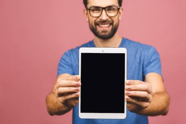 Presentazione del prodotto. promozione. tenuta del giovane in computer della compressa delle mani con lo schermo in bianco, fine su. isolato su sfondo rosa.