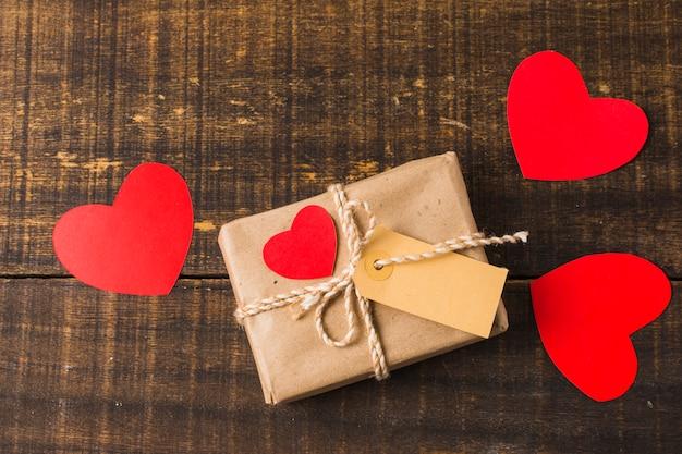 Presente casella e ritaglio di carta avvolti di forma del cuore con etichetta vuota sopra fondo di legno