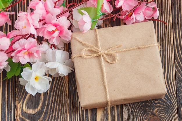 Presente con il mazzo dei fiori su fondo di legno