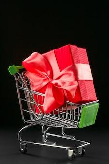 Presente confezione regalo in confezione festiva con fiocco in raso nel carrello.