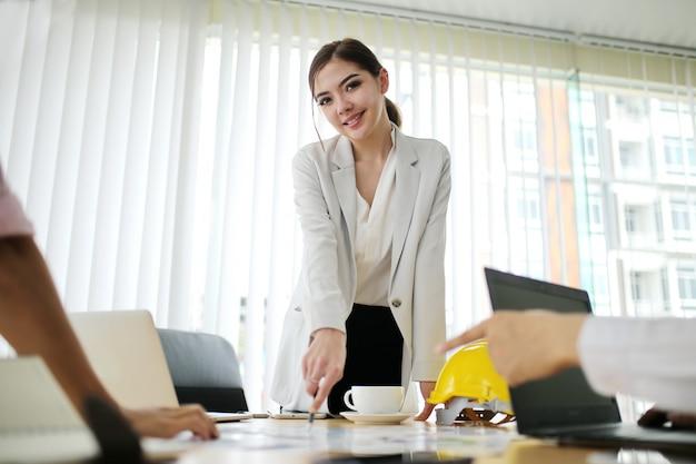 Presente della donna di affari di felicità che spiega i dati finanziari di profitto nell'insieme della sala riunioni.
