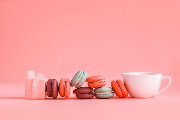 Presente e fila rosa dei maccheroni e della tazza di caffè variopinti francesi