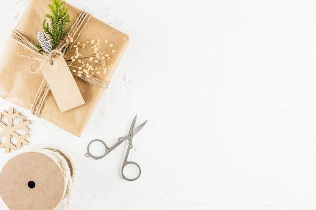 Presente in carta artigianale con tag vicino a forbici e bobina di fili