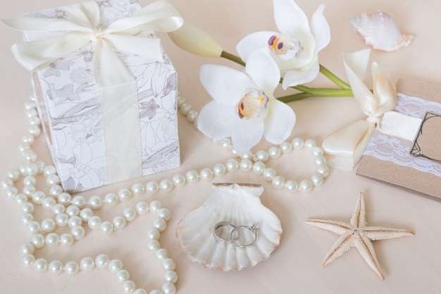 Presente, perline, conchiglie, orchidee e anelli
