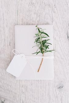 Presente spostato con l'etichetta in bianco e ramoscello su fondo di legno grigio
