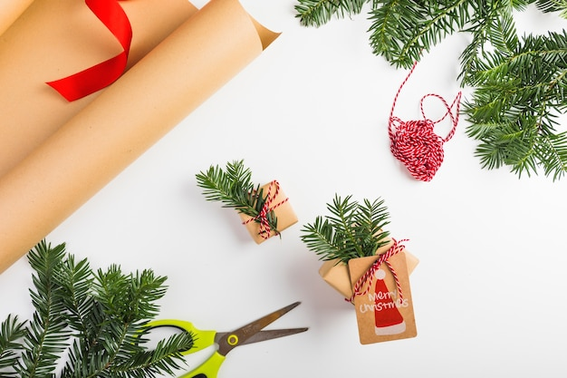Presenti scatole con ramoscelli di abete e fili vicino alla carta artigianale