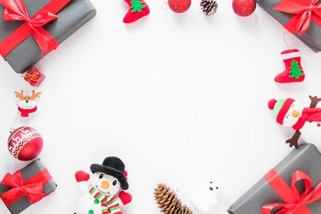 Presenti scatole vicino a pupazzi di neve giocattolo e palla di natale