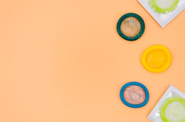 Preservativi colorati vista dall'alto su sfondo arancione