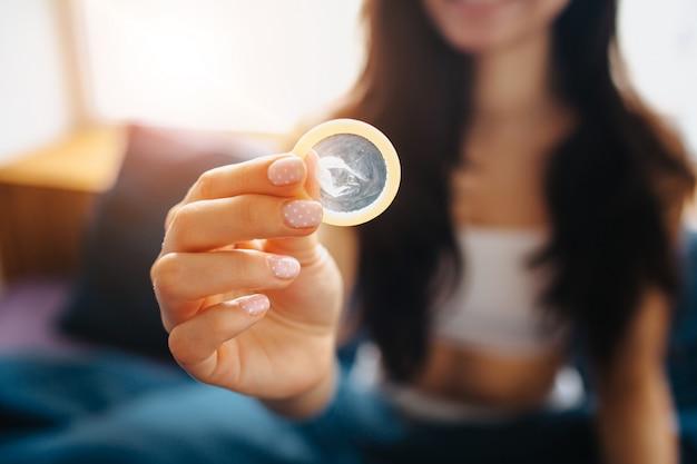 Preservativo della stretta della giovane donna a disposizione. sicurezza sessuale