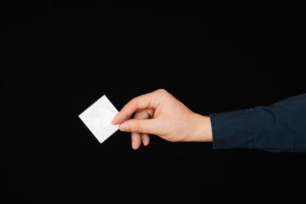 Preservativo per contraccezione e protezione nella mano degli uomini