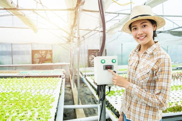 Pressa asiatica del dito della donna sulla macchina del controllo della temperatura in azienda agricola idroponica della serra