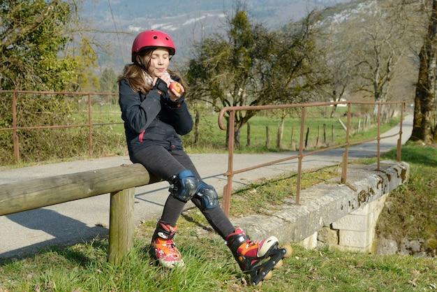 Preteen in roller skate, mangia una mela