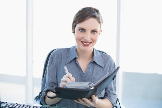 Pretty businesswoman scrivendo nel suo diario seduto alla sua scrivania