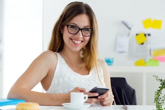 Pretty giovane donna che utilizza il suo telefono cellulare a casa.