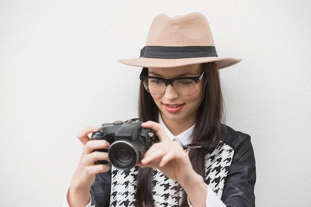 Pretty hipster guardando la sua macchina fotografica