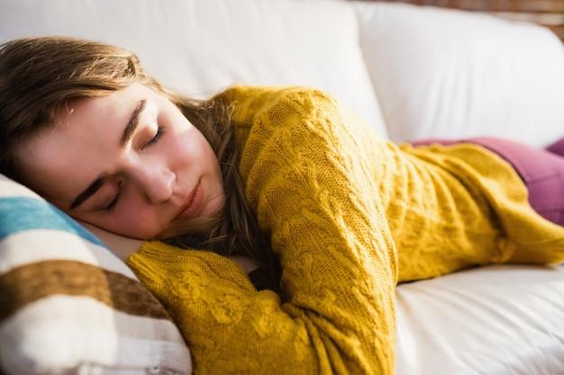 Pretty woman dormendo sul divano in salotto